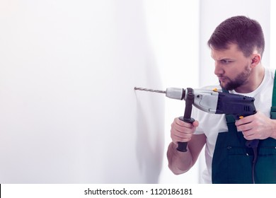 Professional construction worker with drill making a hole in white wall