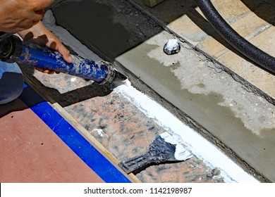 A professional construction worker is fixing an expansion joint, between two buildings, with new cement, and a flexible caulk sealant.