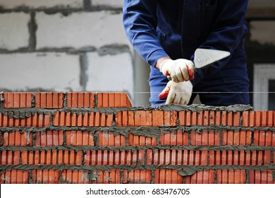 professional construction worker laying bricks and building house on industrial site.