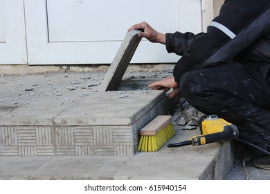 professional construction worker laying stone tiles on the porch at the entrance to the store