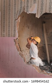 Professional construction worker strong young woman wearing protective personal equipment and safety gear breaking a wall with a large hammer in an old house