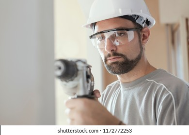 Professional construction worker using a drill, he is wearing a safety helmet and goggles