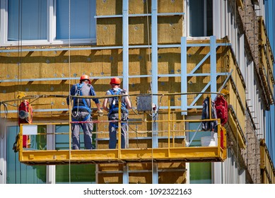 Professional construction workers on the scaffold elevator insulated wall facade with mineral wool. roofers wearing safety harness insulating wall facade at height on old building in a crane.