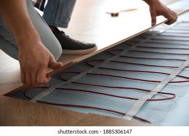 Professional contractor installing underfloor trace heating system indoors, closeup
