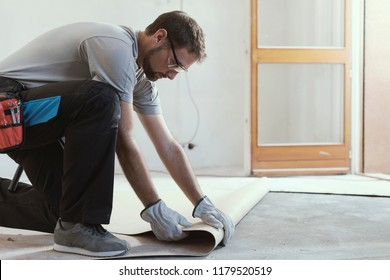 Professional contractor removing an old linoleum flooring: home renovation concept