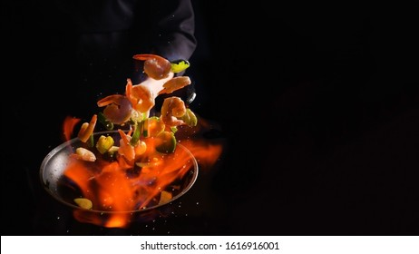 Professional cook cooks shrimps with vegetables on fire. Cooking seafood, healthy vegetarian food, roasting over an open fire. on a dark background. Hotel service, oriental cuisine asia food