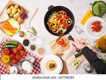 Professional cook frying fresh sliced vegetables in a nonstick pan hands close up, food ingredients and kitchenware on background, top view