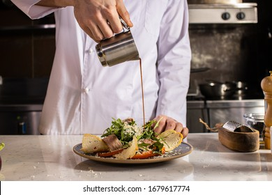 professional cook gently pour the sauce on the salad in the kitchen. cropped man in uniform made vegetarian dish for restaurant visitors