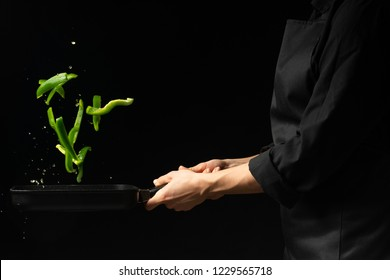 Professional cook. He prepares a dish with green sweet peppers in a saucepan. on black background, menu, recipe book, healthy food