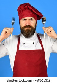Professional cookery concept. Cook with serious face in burgundy hat and apron holds spoon and fork. Chef holds cutlery. Man with beard holds kitchenware on blue background.