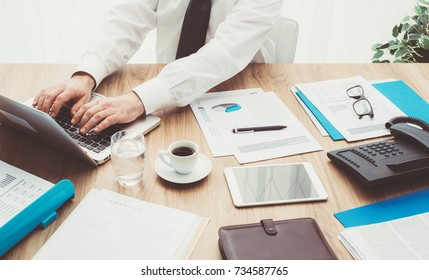 Professional corporate businessman working at office desk, he is using a laptop and analyzing financial reports