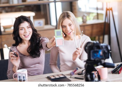 Professional cosmetics. Selective focus of powder being shown to the camera by a cheerful delighted beauty blogger