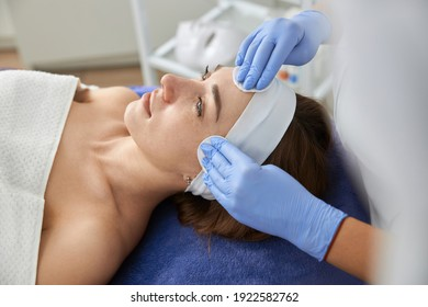 Professional cosmetologist is doing procedures for client in light cabinet