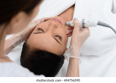 Professional cosmetologist is making cavitation rejuvenation skin treatment. She is lifting equipment over female face. Young woman is lying and relaxing