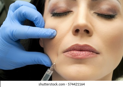 Professional cosmetologist making facial injection