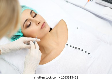 Professional cosmetologist making injection in face, lips. Young woman gets syringe with filler for face contouring or augmentation. Rejuvenation and hydration procedures in cosmetology