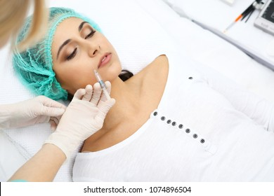 Professional cosmetologist making injection in face, lips. Young woman gets syringe with filler for face contouring or augmentation. Face aging, rejuvenation and hydration procedures