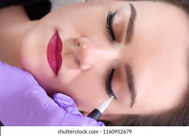 Professional cosmetologist wearing purple gloves making permanent eyeliner makeup for young woman. Client lying on couch at beauty salon and enjoying. Close up, selective focus