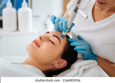 Professional cosmetology. Smart skilled cosmetologist using a modern device while doing hydrafacial procedure