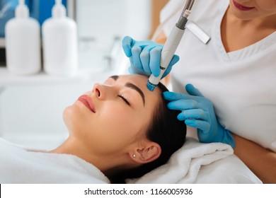 Professionelle Kosmetologie. Intelligenter Kosmetologe, der ein modernes Gerät verwendet und gleichzeitig Hydrafaceverfahren durchführt