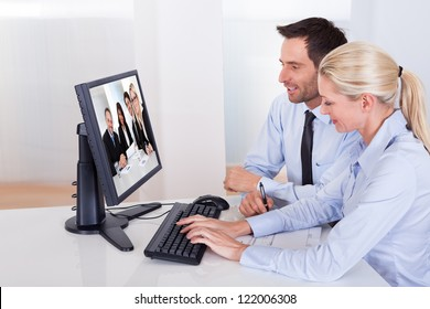 Professional couple sitting together at a desk watching an online presentation on the computer monitor