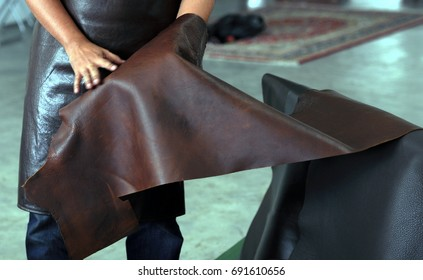 Professional crafter choosing brown cow leather for making leather items