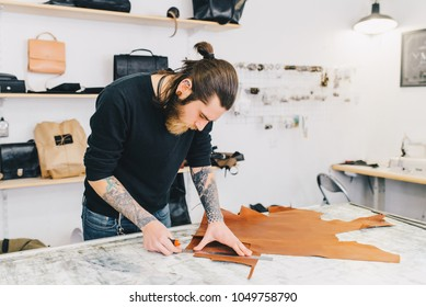 Professional crafter making leather items