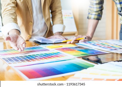 Professional Creative architect graphic desiner occupation choosing the Color pantone  palette samples for project on office desktop computer