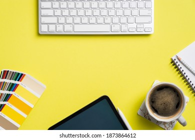 Professional creative graphic designer desk with computer keyboard, tablet, color palette, cup of coffee, notebook on yellow background. Flat lay, top view.