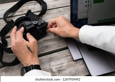 Professional creative profession freelancer, photographer or videographer extracts or takes out memory card from camera, ready to transfer files and images on new laptop