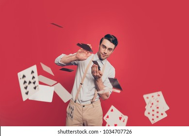 Professional, cunning magician, illusionist, gambler in casual outfit, glasses, throwing, sending cards to the camera, standing over red background