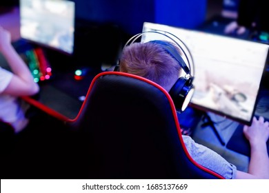 Professional cyber video gamer studio room with personal computer for stream in neon color blur background. Soft focus.