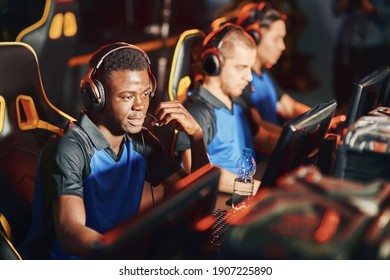 Professional cybersport gamer wearing headphones talking by microphone with team member while playing online video game. eSport tournament concept
