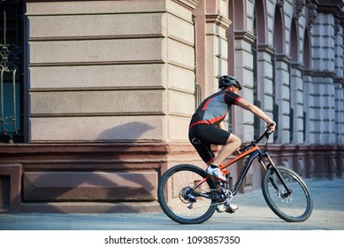 Professional cyclist in cycling garment and protective gear riding bicycle in city center rushing and passing buildings. Sportsman training, exercising outdoors. Concept of healthy lifestyle