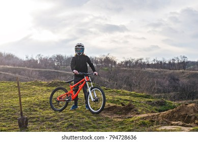Professional cyclist in helmet, prepare for the beginning of descent from the top of the mountain. Downhill Extreme sport.