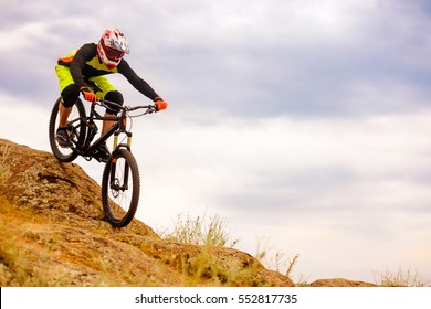 Professional Cyclist Riding the Bike Down Rocky Hill. Extreme Sport Concept. Free Space for Text.