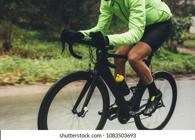 Professional cyclist riding bike outdoors. Male athlete in cycling gear practising on wet road. Cropped shot.