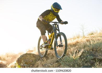Professional Cyclist Riding the Downhill Mountain Bike on the Summer Rocky Trail at the Evening. Extreme Sport and Enduro Cycling Concept.