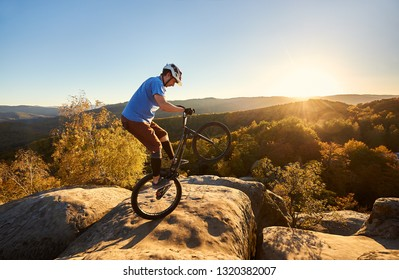 Professional cyclist riding on back wheel on trial bicycle. Sportsman rider balancing on the edge of big boulder on the top of mountain at sunset. Concept of extreme sport active lifestyle