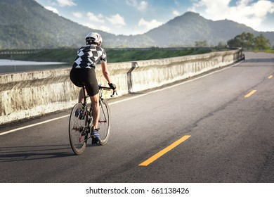 Professional cyclist riding racing bike in race competition on open road. Sports athlete man biking with high intensity on highway during summe
