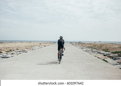 Professional cyclist spins toward the sea on open seaside boardwalk