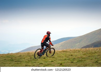 Professional cyclists riding the downhill mountain bike on the mountain trail. Two cyclists are preparing to ride mountain bike on single trail in Carpathians, Borzhava, Ukraine.