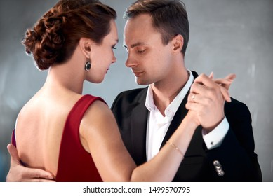 Professional dancers of argentinian tango moves at the dance floor in black and red stylish clothes