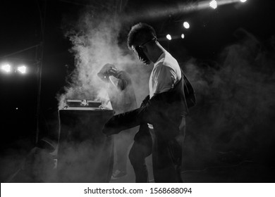 Professional dancers - young white guys in masks is dancing emotional inflammatory club dance on stage during a dubstep party, DJ, black and white, rhythm, tempo, movement, happiness, performance, PJ