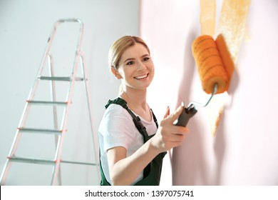 Professional decorator painting wall indoors. Home repair service