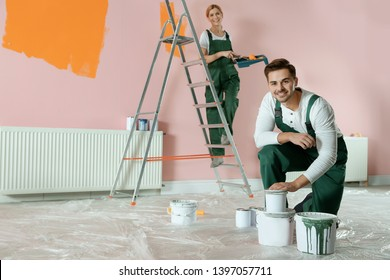 Professional decorators painting wall indoors. Home repair service