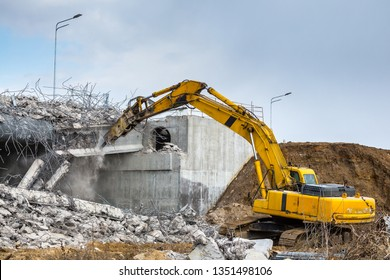 Professional demolition of reinforced concrete structures using industrial hydraulic hammer. Rods of metal fittings. Wreckage and crumbles of concrete.