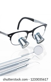 Professional dentist's medical tools, loupes, surgical loupes, dental probe and dental mirror on white background. Dental hygiene, tartar and plaque, preventing concept.Periodontics dental hy