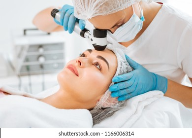 Professional dermatology. Pleasant young woman having her skin checked while visiting a dermatology clinic
