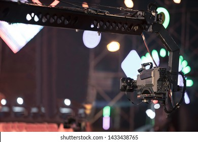 Professional digital camera in crane recording video in music concert festival
